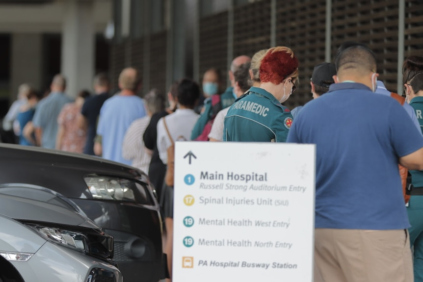 A line of people with sign pointing to main hospital.