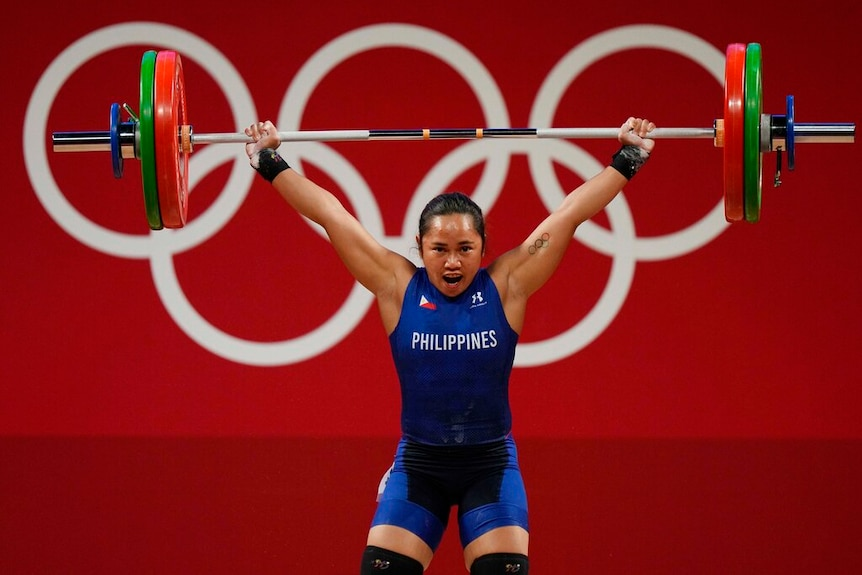 Hidilyn Diaz holds weights above her head.