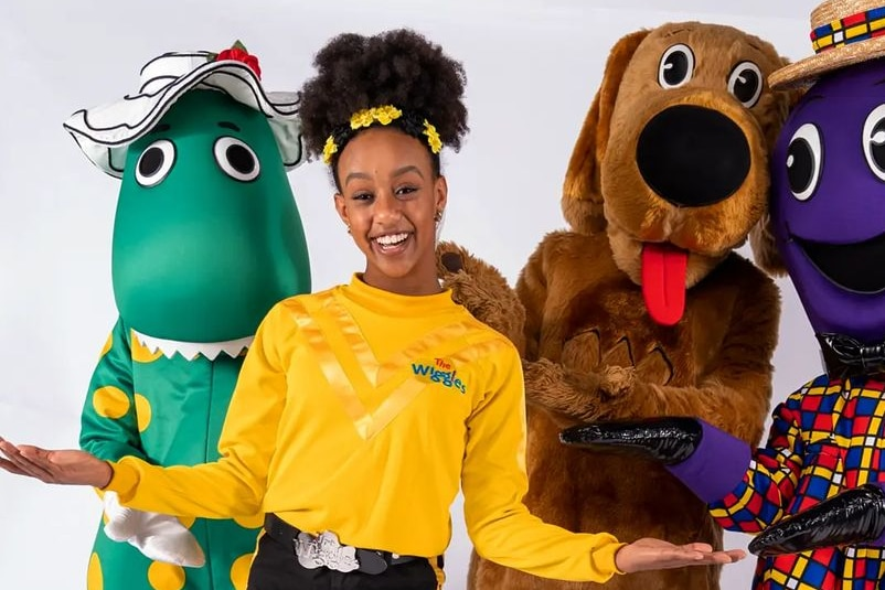 A woman with dark afro hair wearing a yellow top standing with dorothy the dinosaur, wags the dog and henry the octapus.