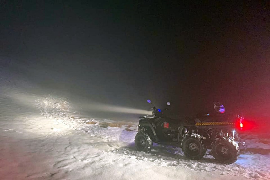A snowmobile with its lights glowing in the dark.
