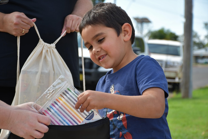 A young child pull a pack of crayons out of a bag.