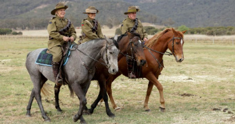 Three people in uniform ride three horses in the capertee valley