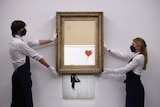 Two people hold a Banksy art on the wall