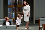 Anika Wells holds the hand of her young daughter on the floor of the House of Representatives.
