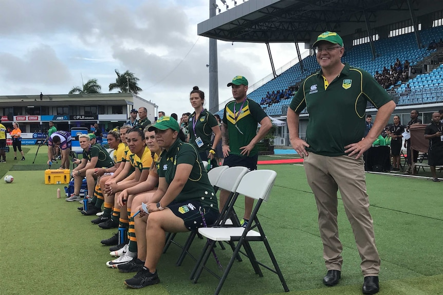 Scott Morrison at ANZ National Stadium in Suva. He is standing on the field with some Australian Rugby League players.