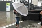 A woman hides under an umbrella in heavy rain.