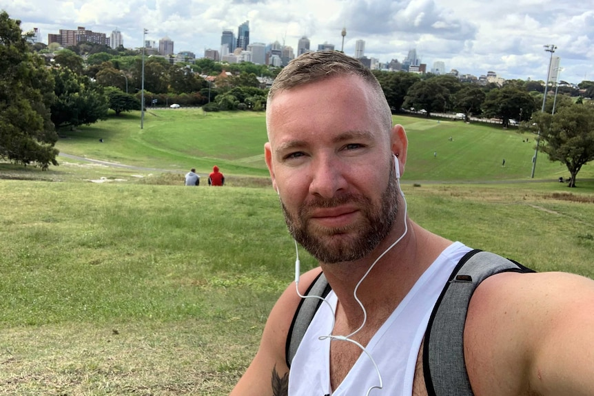 Mr Woodward is picture taking a selfie in a park in Sydney.