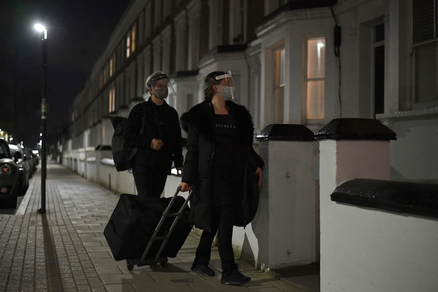 Two people walk on a London street with luggage wearing face shields