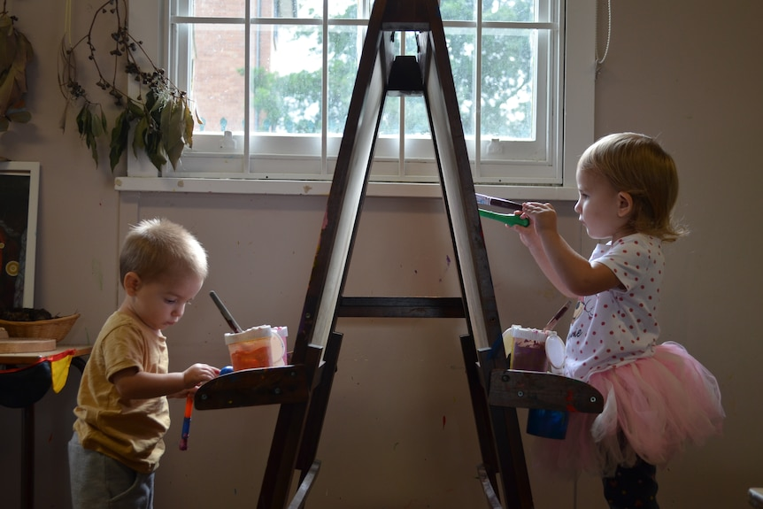 Two children paint infront of window facing each other