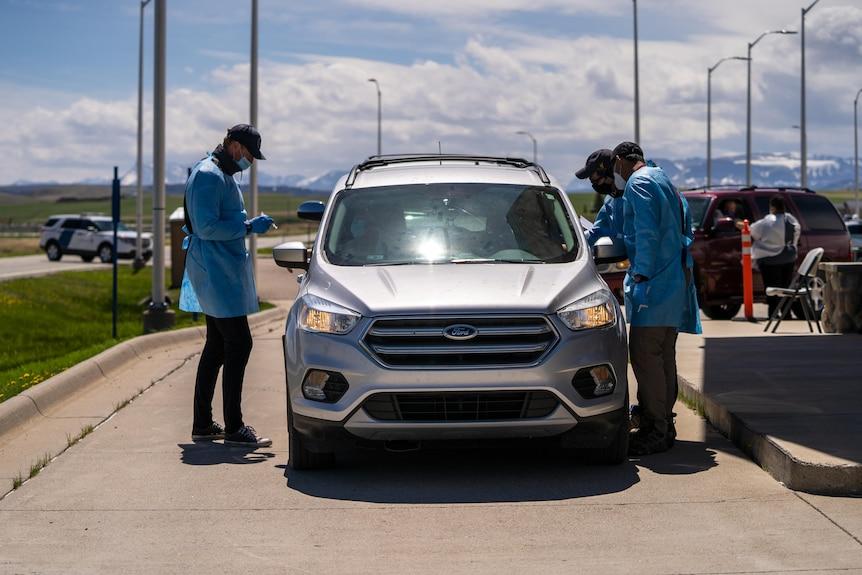 Operatori sanitari in piedi fuori da un'auto in una clinica per vaccini dall'auto.