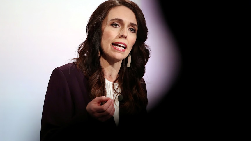 Woman in a black business jacket and white top speaks during a political debate.