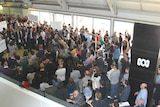 Hundreds of people gathering, some holding protest signs in a building with the ABC logo.
