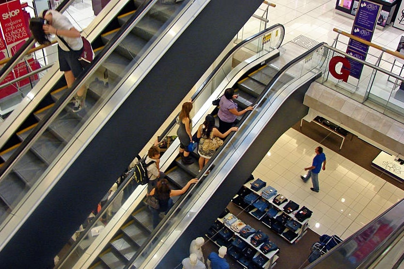 Shoppers on escalators in a shopping centre