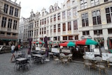 Empty tables and chairs in Brussels' Grand Place square.