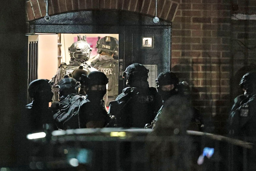 A swat team enters a brick building at night.