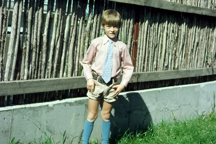 A 1970s photo of a young boy in a garden, dressed in a shirt, tie and shorts.