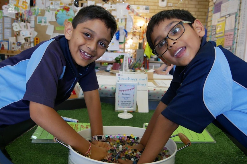 Two boys in class at Beaumaris Primary School pose for a photo smiling wearing blue uniforms.