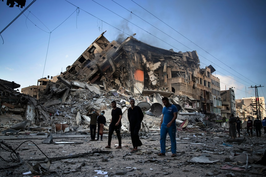 A group of men walk next to the ruins of a large building in Gaza