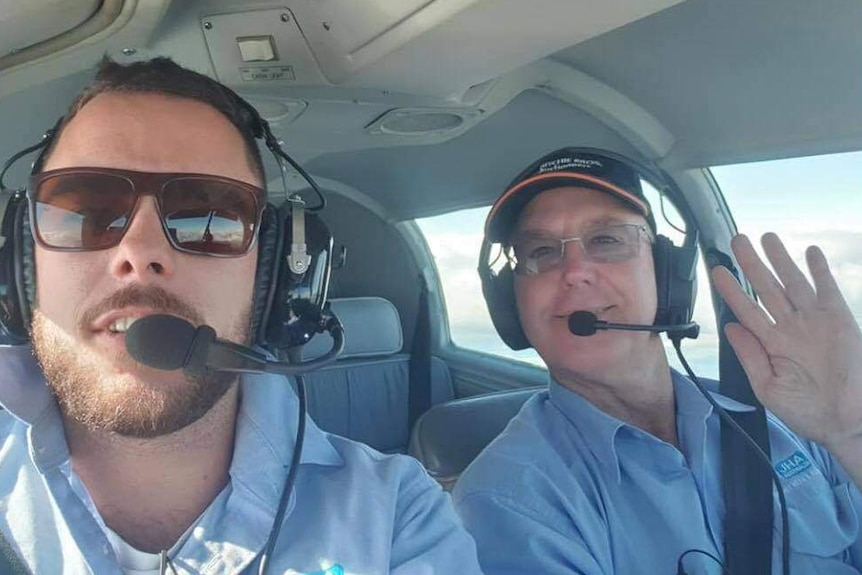 a young man and his father sitting in a plane