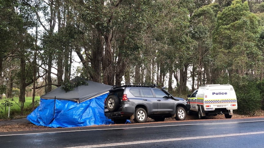 A tent with a tarpaulin pulled around it protects the scene. A black 4wd and police car are parked nearby.