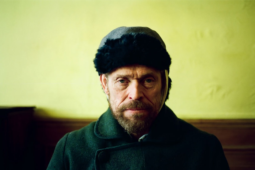 Colour still of Willem Dafoe sitting in front of yellow wall as Vincent Van Gogh in 2018 film At Eternity's Gate.