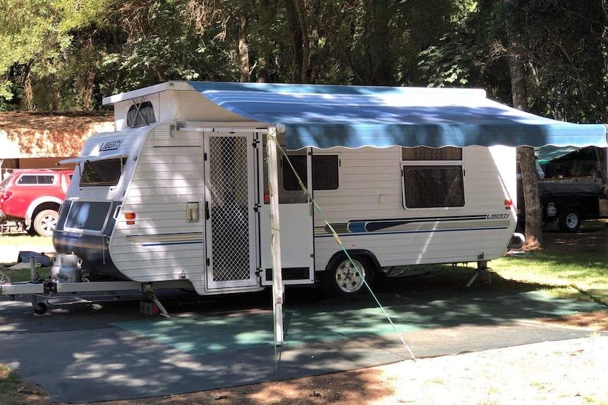 A caravan with an awning, in a caravan park