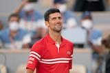 A smiling Novak Djokovic walks towards the net after winning the French Open.