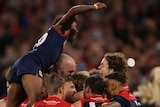 Kysaiah Pickett jumps on a pack of celebrating Melbourne Demons after the AFL grand final.