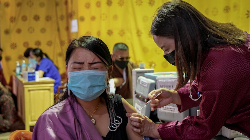 A health worker innoculates a woman with the COVID-19 jab at a vaccine center in Thimpu on july 26.
