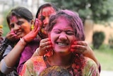Indian girls play with colored powder during Holi festival