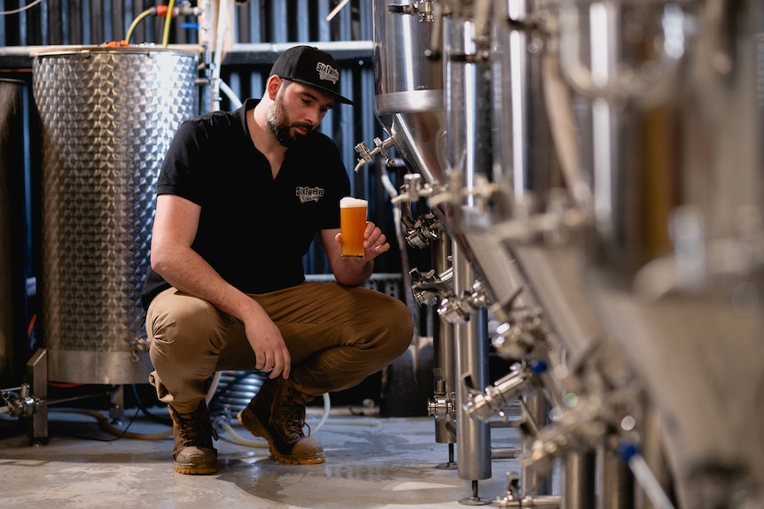 A man studies a beer poured from a tap adjacent stainless steel tanks