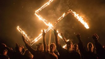 Several people give a Nazi salute in front of a burning swastika.