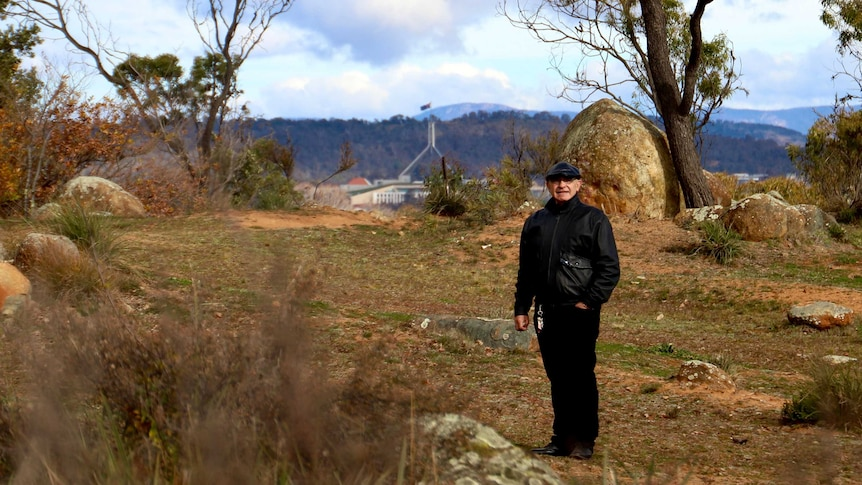 A man wearing stands in a clearing surrounded by rocky outcrops, with Parliament House visible in the distance.