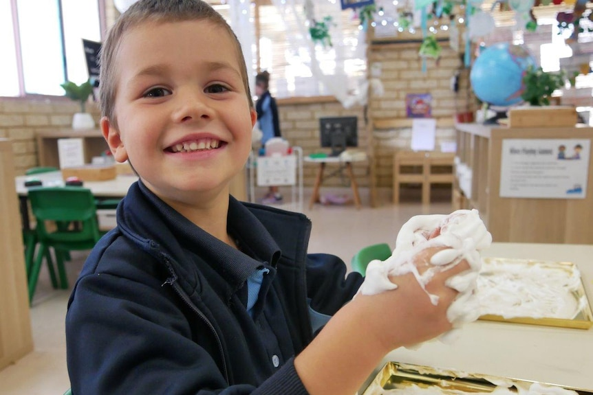 A boy smiles sitting at a table in a classroom grasping a white foam-type substance in his hands.