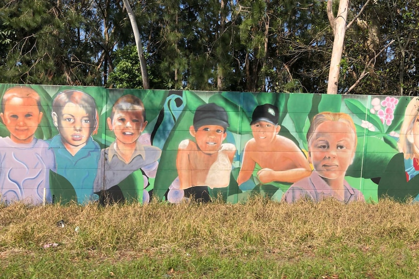 Street art of children's faces painted on a highway soundwall.