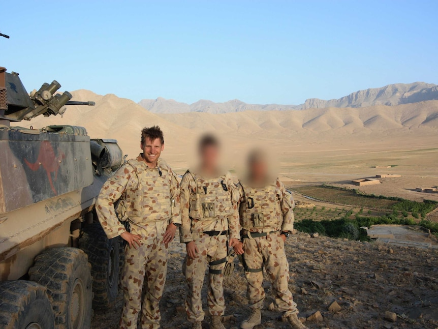 Three soldiers standing next to a tank in a valley  in front of large brown mountains