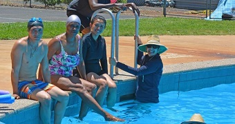 Five people dressed in swimming attire sit on the edge of a public swimming pool