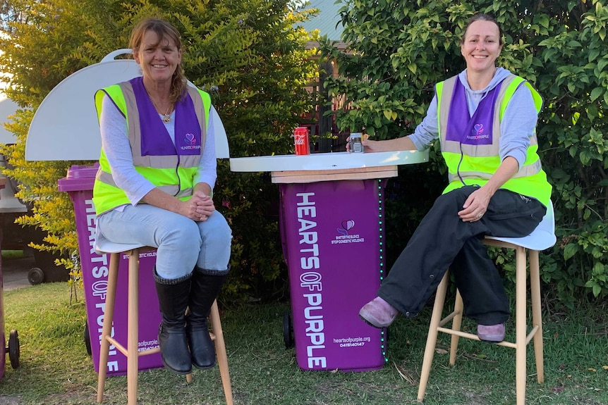 two women sit around a purple wheelie bin with a table top and writing on side of the bin that says hearts of purple