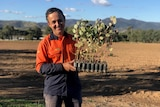 A man stands smiling, holding young trees ready to plant.