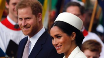 Prince Harry wears a suit, Meghan a white dress and white hat.