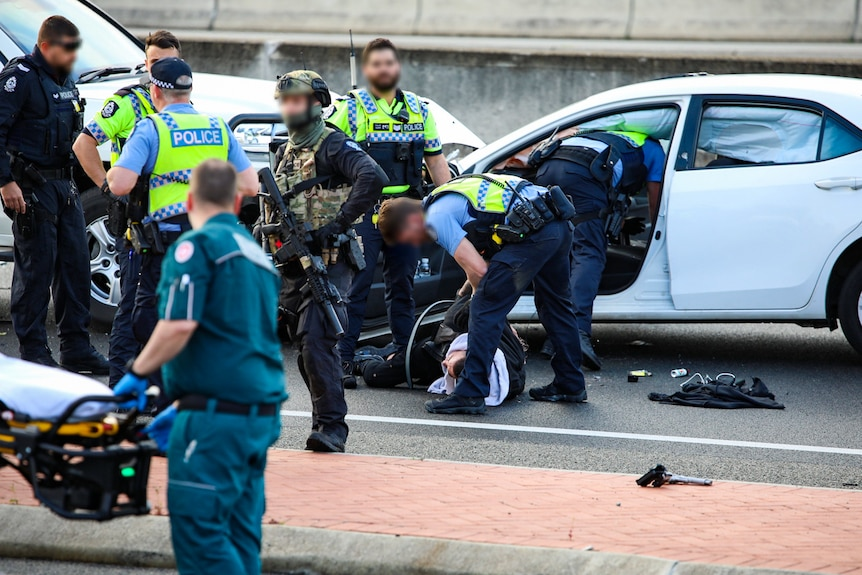 A police officer bends down to speak to a man on the ground.