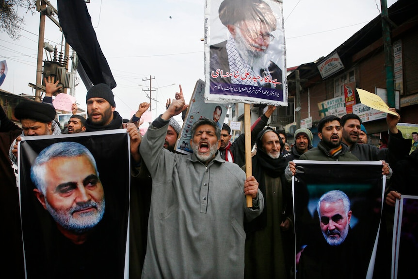 A large crowd of men carry placards showing the image of Qassem Soleimani as they raise their hands mid-shout.