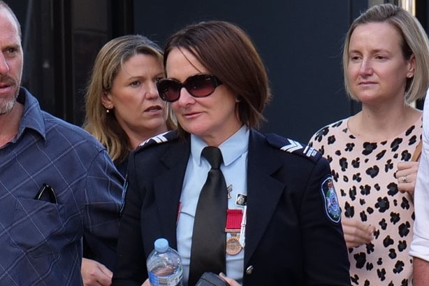 Senior Constable Catherine Nielsen in uniforms leaves court wearing sunglasses.