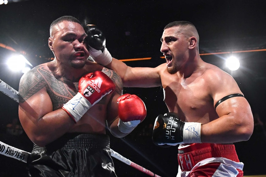 Faiga Opelu's (left) face is contorted as Justis Huni (right) lands a right-hand punch.