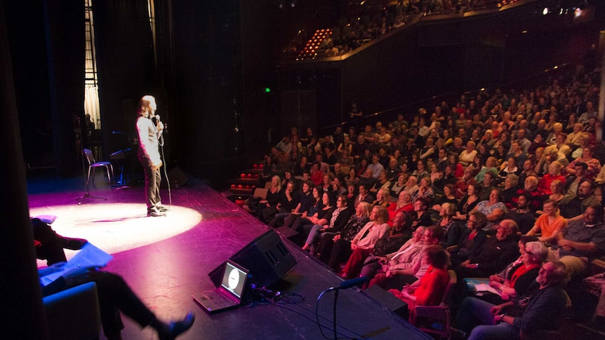 A man in a spotlight performs onstage to a crowd.