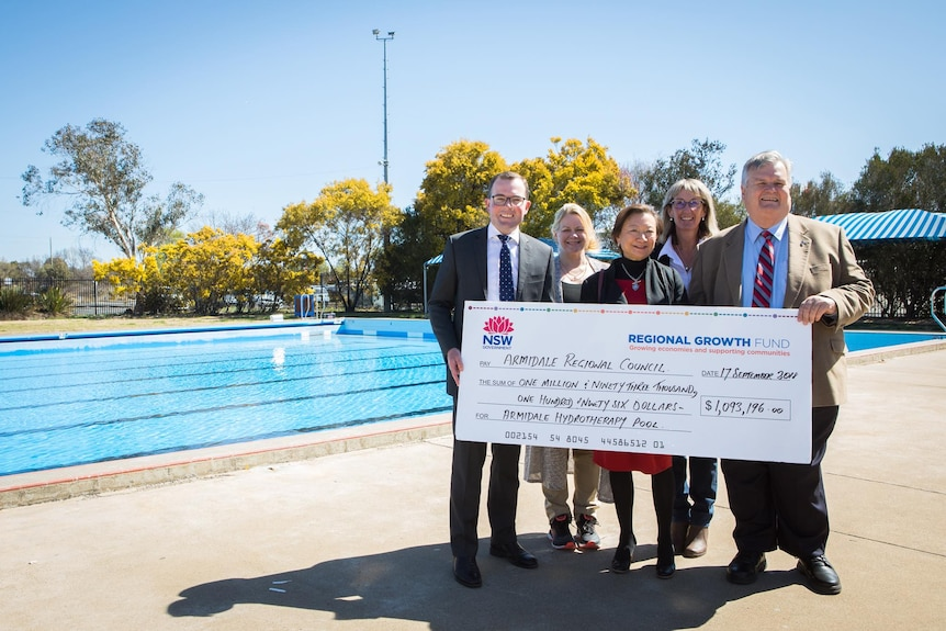 Three women and two men stand smiling, holding a large novelty cheque in front of a pool.