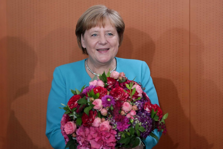 German Chancellor Angela Merkel holds a bunch of flowers that she received as a birthday present.