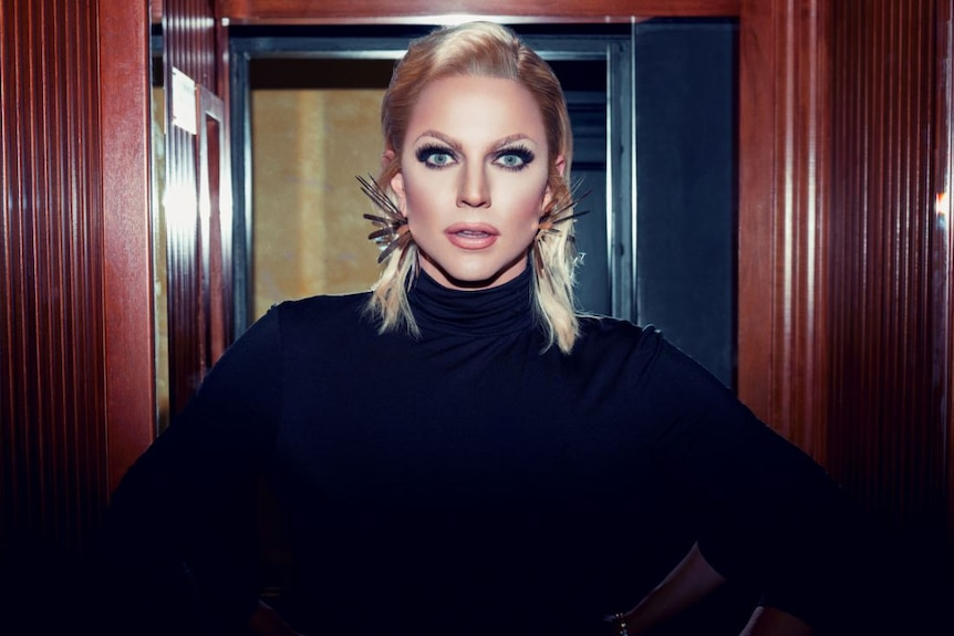 Shane Jenek dressed as Courtney Act, staring straight into the camera.