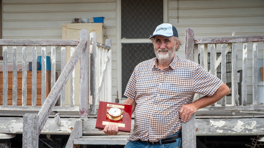 Warwick farmer Gerard Walsh at his farm house holding his award from the Bureau of Meteorology in February 2021.