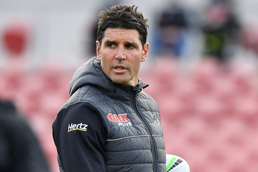 A Penrith Panthers NRL assistant coach looks to his right as he holds two footballs with his left arm.